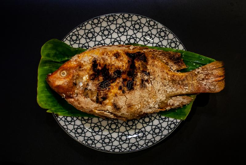 Tilapia fish grilled on banana leaf in a beautiful plate, Thai foods style placed stock images