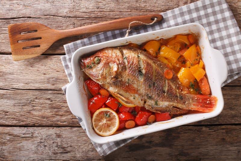 Tilapia ryba piec z dzwonkowymi pieprzami, marchewkami i macierzanki zamkniętym up, fotografia stock