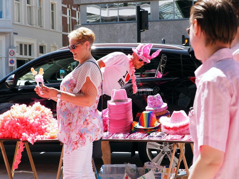Pink Monday on the annual funfair in Tilburg, Netherlands. Tilburg, Netherlands - July, 22, 2019: Woman has just bought a pink assecoire at a pop up market stall stock photos
