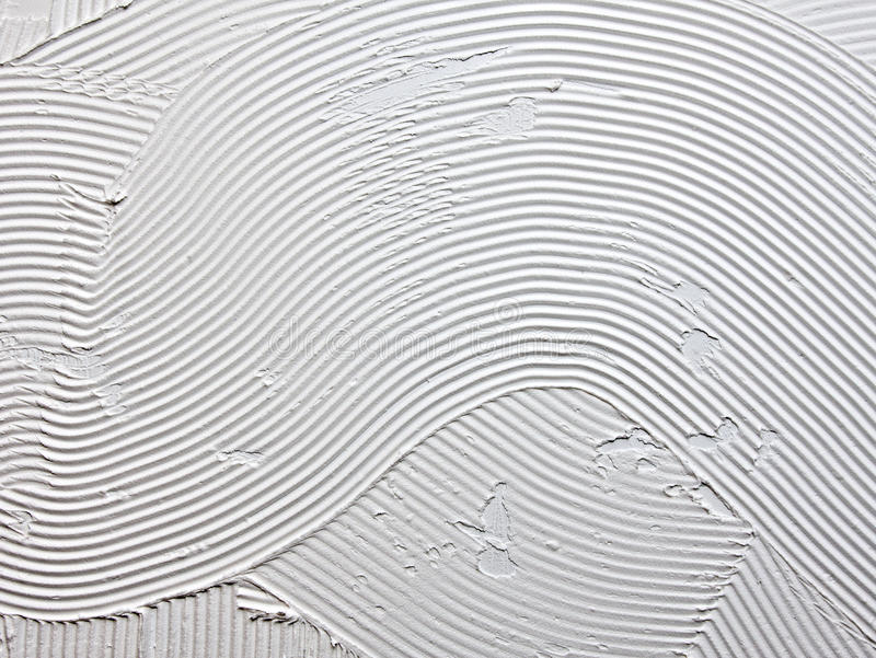Tile adhesive. Makes abstract pattern with v groove trowel stock photo