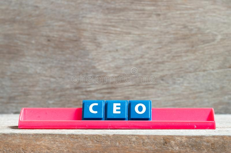 Tile letter on rack in word CEO abbreviation of Chief Executive Officer on wood background. Tile letter on red rack in word CEO abbreviation of Chief Executive royalty free stock photography
