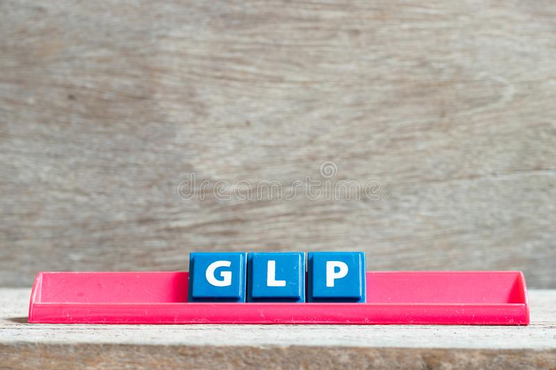Tile letter on rack in word GLP Abbreviation of Good laboratory practice on wood background. Tile letter on red rack in word GLP Abbreviation of Good laboratory royalty free stock photo
