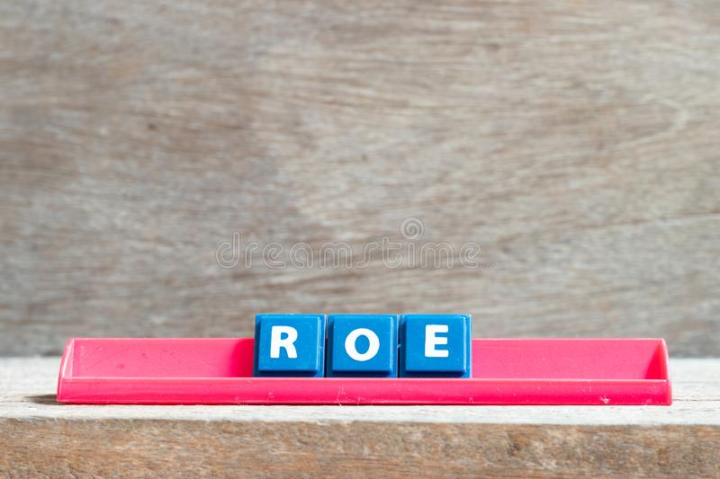 Tile letter on rack in word ROE Abbreviation of Return on equity on wood background. Tile letter on red rack in word ROE Abbreviation of Return on equity on wood stock image
