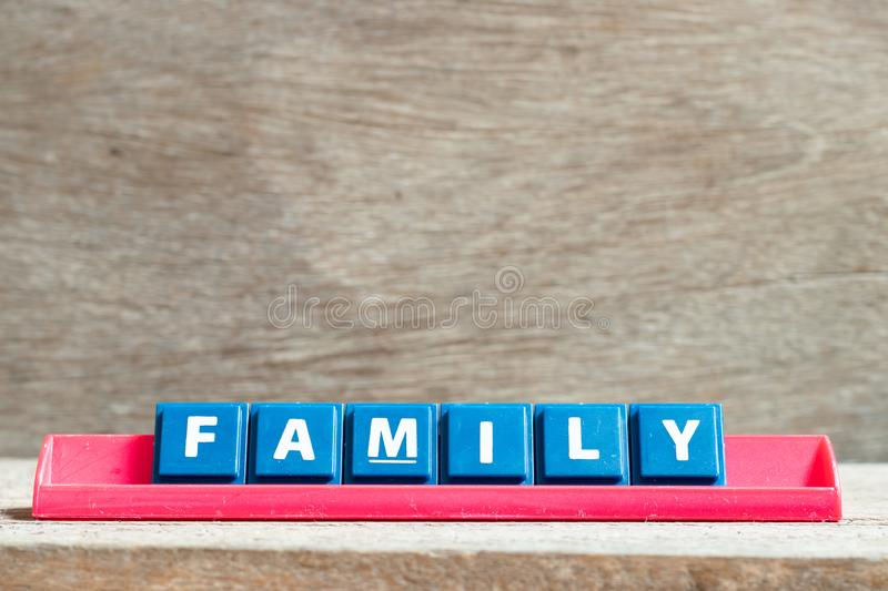 Tile letter on rack in word family on wood background. Tile letter on red rack in word family on wood background stock image