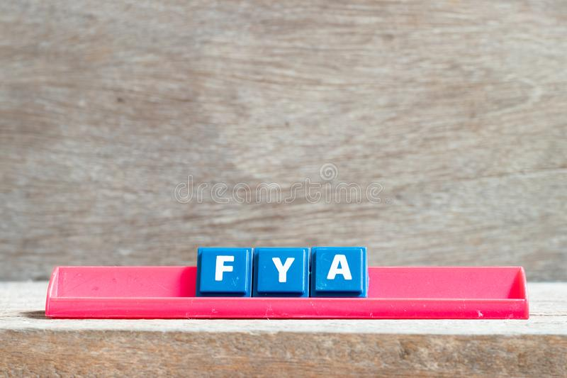 Tile letter on rack in word FYA Abbreviation of For your action or attention on wood background. Tile letter on red rack in word FYA Abbreviation of For your royalty free stock photos