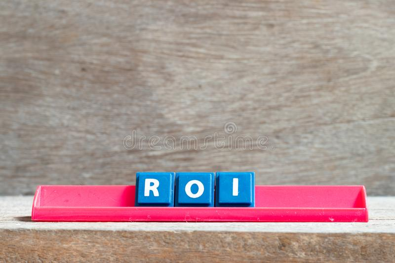 Tile letter on rack in word ROI Abbreviation of Return on Investment on wood background. Tile letter on red rack in word ROI Abbreviation of Return on Investment stock photo