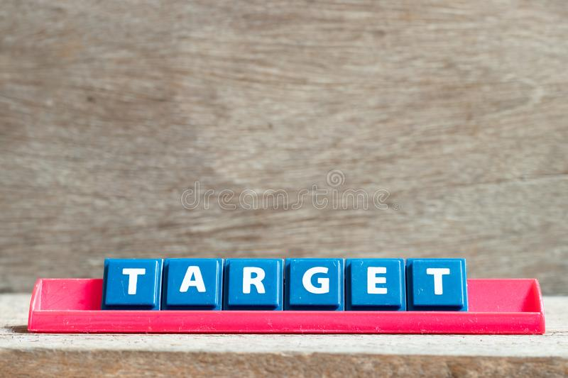Tile letter on rack in word target on wood background. Tile letter on red rack in word target on wood background stock image