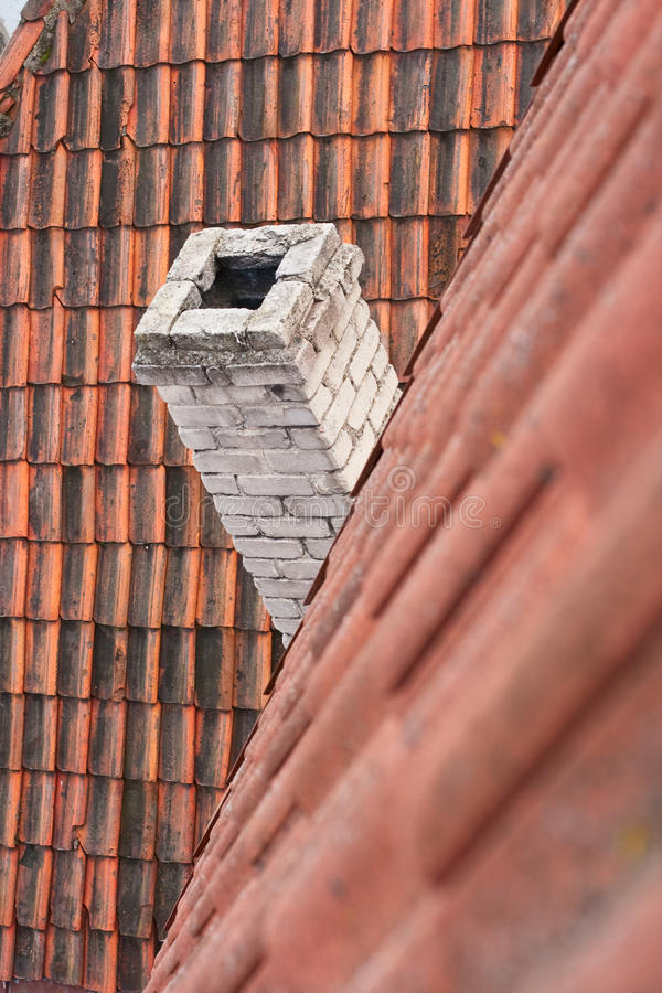 Tile roof and chimney. Tile red roof and brick chimney. Small abstraction stock photography