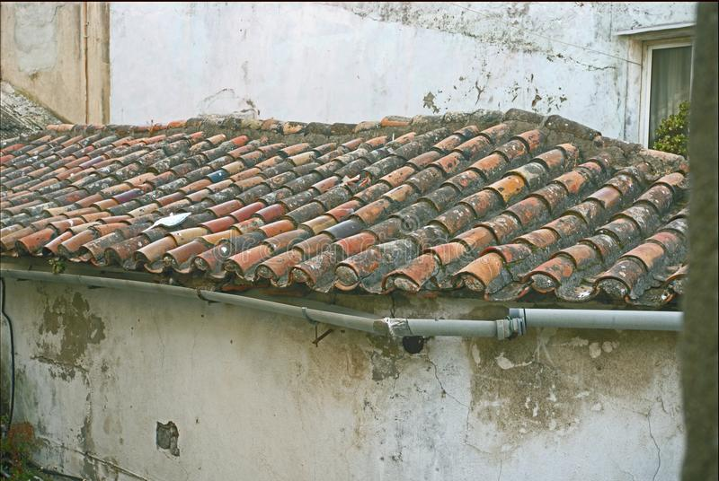 A red Tile roof with a water drain stock images