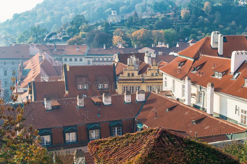 Tiled brown roofs of old houses in the autumn morning in Prague. Tiled brown roofs of old houses in autumn morning in Prague, architecture, autumnal, blue stock images