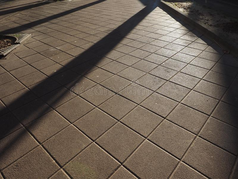 Tiled floor pavement background. Tiled floor pavement at night with shadows useful as a background stock images