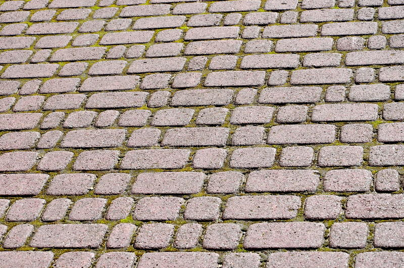 Tiled pavement background. Stone paving royalty free stock images