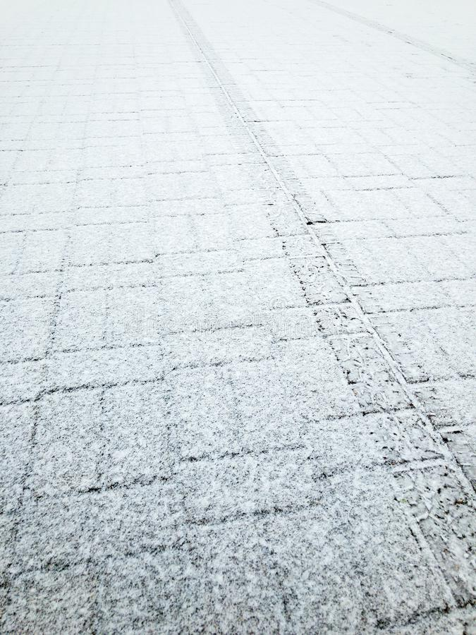 Tiled pavement covered with first snow. tyre track imprint on surface. Of sidewalk stock photo