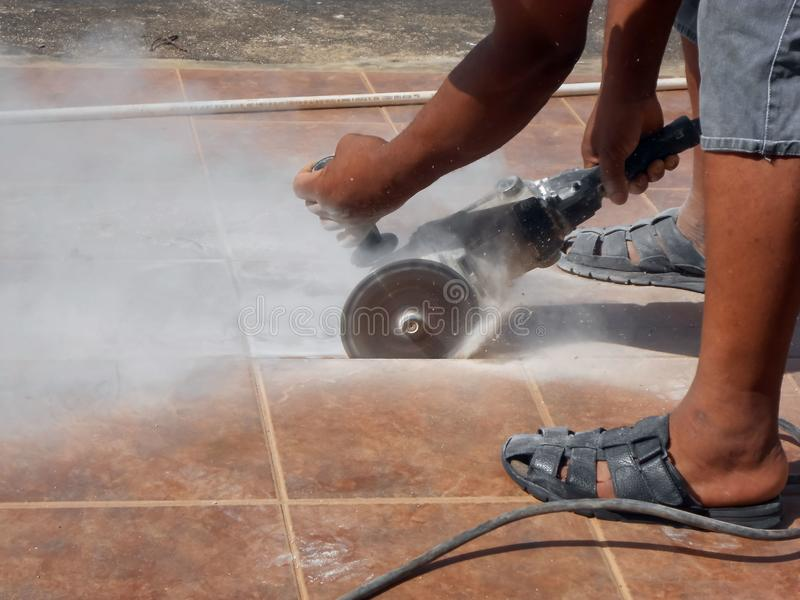 Tiled Pavement Cutting With Power Saw. Thick white dust propels and left suspended in the air as the spinning disk of a power saw slices through the tough, brown royalty free stock photos
