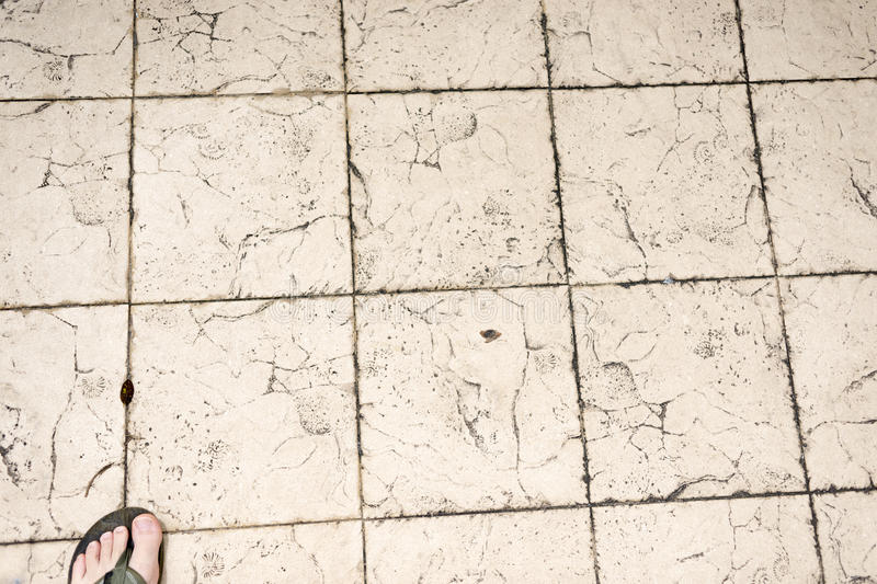 Tiled pavement floor. With toe in slipper in the corner royalty free stock photo