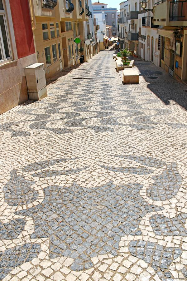 Tiled pavement in Lagos, Portugal. Street of Lagos with tiled pavement, Algarve, Portugal royalty free stock image