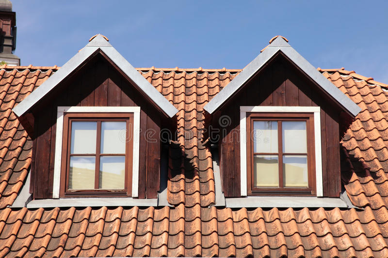 Tiled roof and garret windows in old house. Orange tiled roof on blue sky and garret windows in old house, Vilnius royalty free stock photos