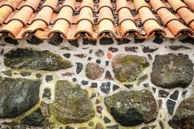 Tiled roof and wall decorated with stones. royalty free stock image