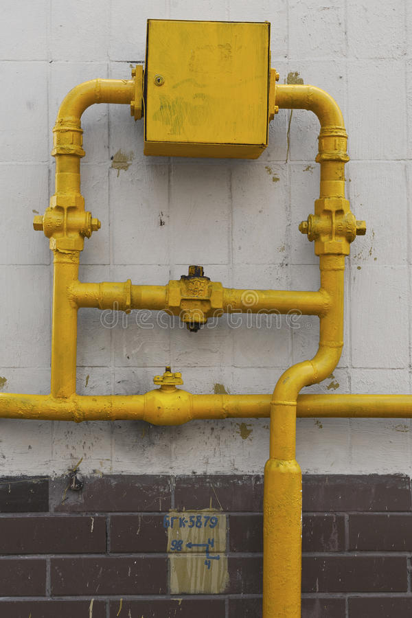 Tiled wall with a gas pipe valves. Painted tiled wall with a gas pipe valves stock photos