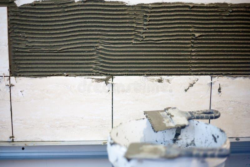 Tiler кладет керамическую плитку стоковые изображения