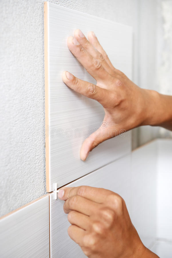 Tiler hands at home renovation work. Close-up view of tiler hands fixing wall tile with spacers at home repair renovation work stock photo