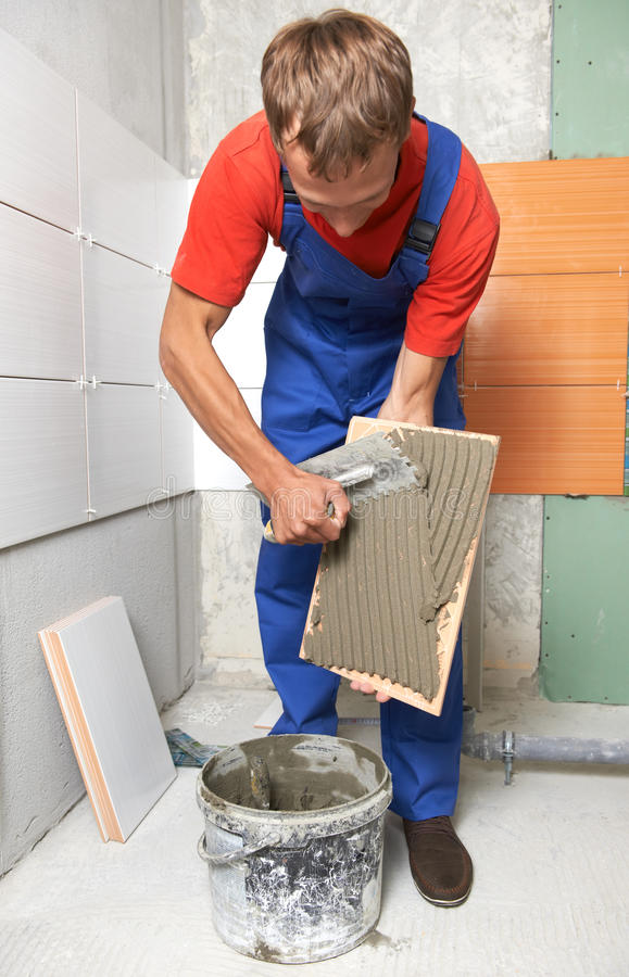 Tiler at home renovation work. Tiler putting glue mortar on tile during wall decoration at home repair renovation work royalty free stock photography