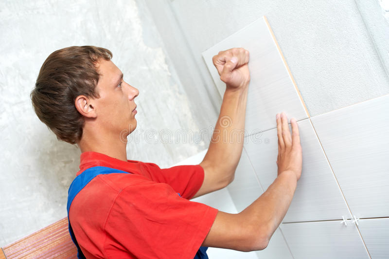 Tiler at home renovation work. Tiler fixing wall tile at home repair renovation work stock photo