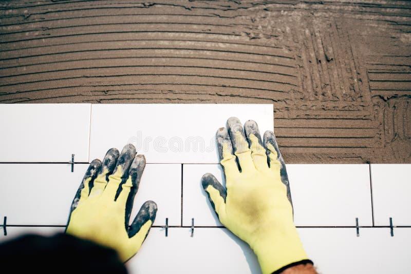 Tiler industrial, guardando e instalando telhas cerâmicas do banheiro durante a renovação fotografia de stock royalty free