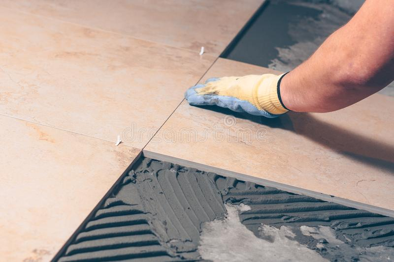 The tiler puts the tile on the floor stock photos