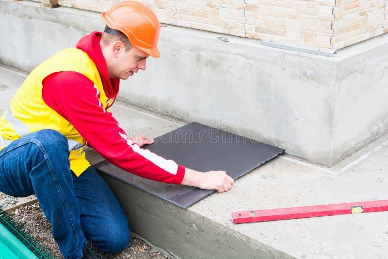 Tiler que instala telhas cerâmicas foto de stock