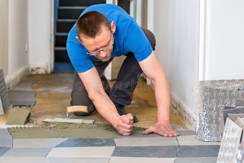 Tiler que instala telhas de assoalho cerâmicas fotos de stock