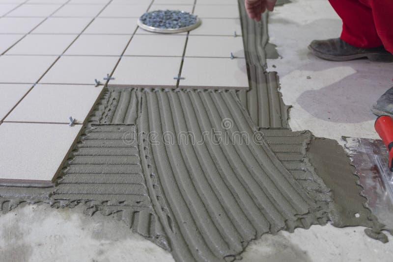 Tiler som installerar keramiska tegelplattor på ett golv arkivfoto