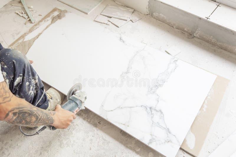 Tiler som klipper en golvtegelplatta med en bärbar vinkelmolar Hantverkarehänder som använder elkraft, såg på keramiska tegelplat fotografering för bildbyråer