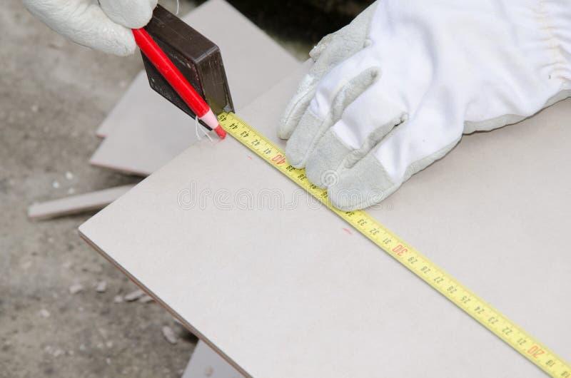 Tiler som mäter tegelplattan, innan att klippa arkivfoton