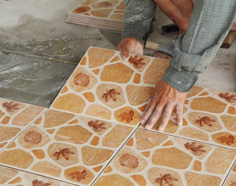 Tileren installerar keramiska tegelplattor arkivfoto