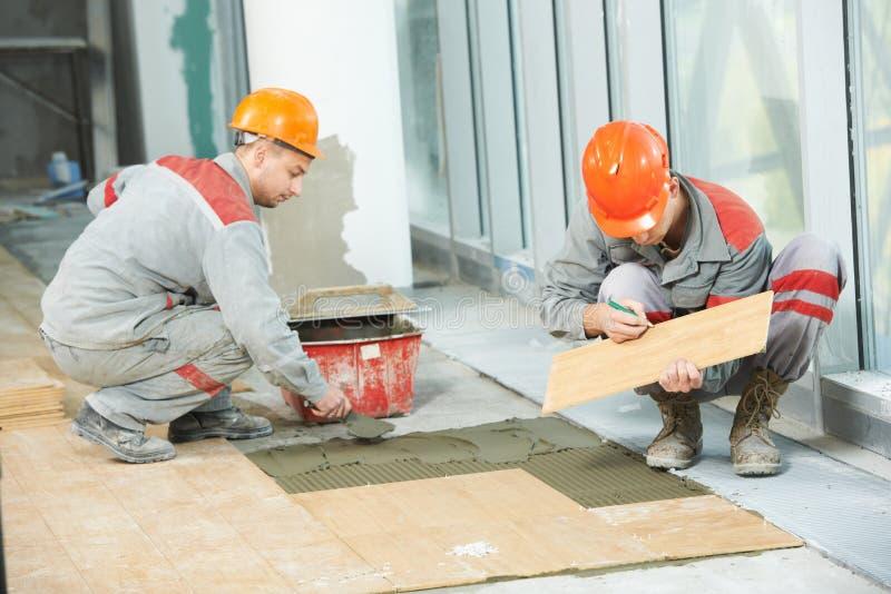 2 tilers на промышленной реновации tiling пола стоковое фото rf