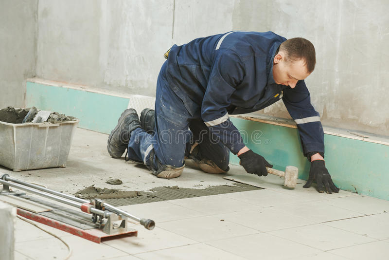 Tilers på det industriella golvet som belägger med tegel renovering arkivfoton