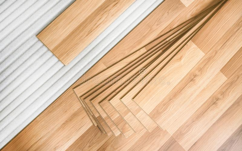 Tiles of laminated floor with wooden effect laying on white base foam, ready to be installed, top down view - home stock photos