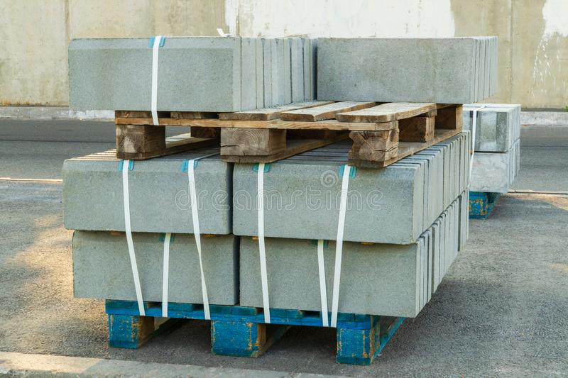 Tiles piled in pallets, warehouse paving slabs in the factory for its production. Gray tiles piled in pallets, warehouse paving slabs in the factory for its royalty free stock photo