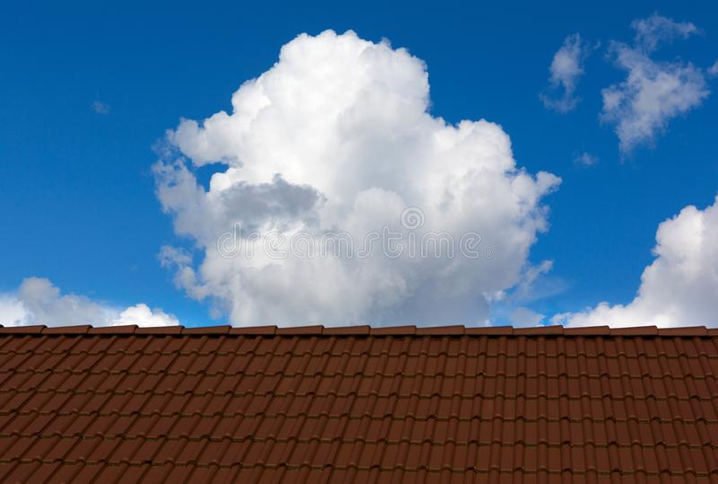 Tiles roof and sky on sunny day. Roof house with blue sky and clouds.  Tiles roof and sky on sunny day royalty free stock images