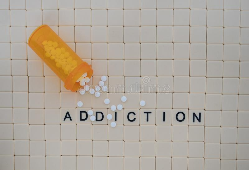 Tiles in a Row Spelling Addiction and White Tablets on a Tile Ba stock image