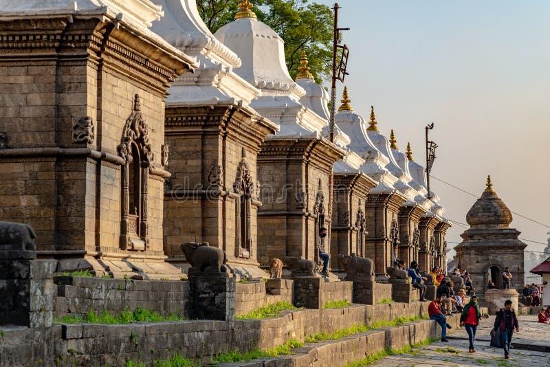Several small temples protecting Shiva Lingam at Pashupatinath temple. TILGANGA, KATHMANDU, NEPAL - APRIL 2, 2019: Visitors and several small temples protecting stock image