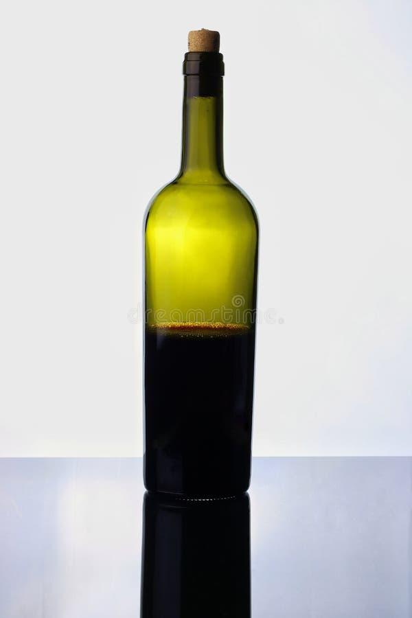 till hälften tom rött vinflaska på vit royaltyfria bilder