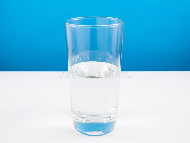 Till hälften tomt eller halvfullt exponeringsglas av vatten på den vita tabellen (För att tänka för realitet) arkivbild