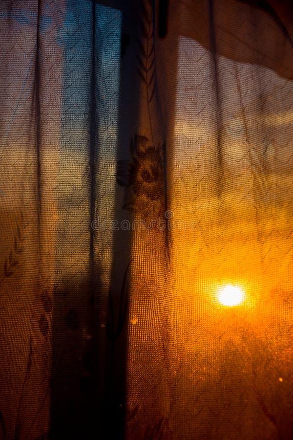 Till och med gardinen skiner inställningssolen royaltyfri fotografi