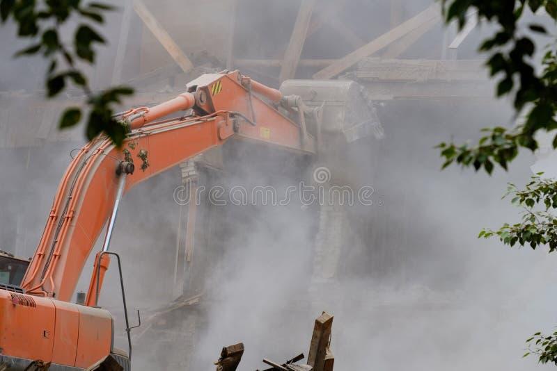 Till och med träden på förgrunden är en grävskopahink som bryter byggnaden, demontering av skadade byggnader, damm och stenen arkivfoton