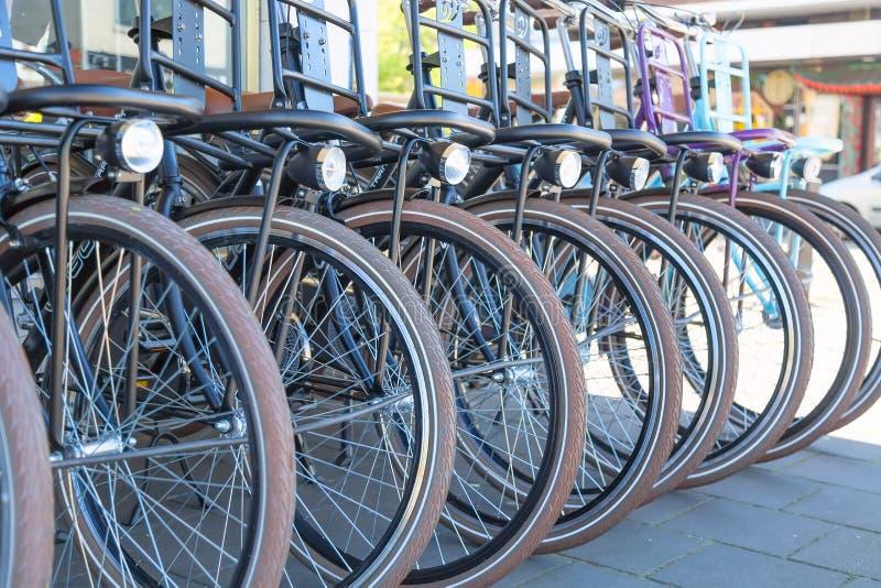 Till salu cyklar eller att hyra i stadsgatan av Amsterdam, Nederländerna Iconic transport i Amsterdam arkivbild