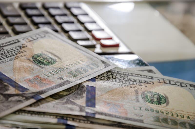 Till salu lagerf?ra fotoet Räknemaskin dollar på finansiella diagram N?rbild ?gander?tt f?r home tangent f?r aff?rsid? som guld-  royaltyfri bild