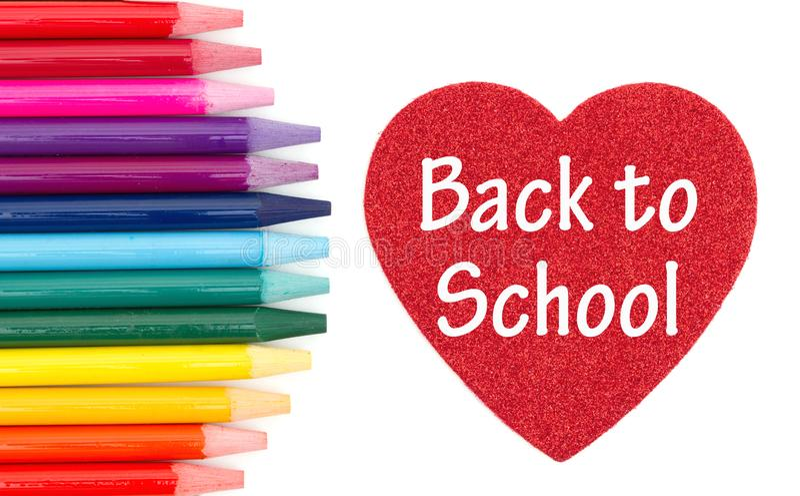 Tillbaka att skola meddelandet på röd hjärta med kulöra vattenfärgblyertspennor arkivfoto