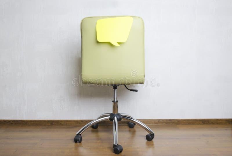 Tillbaka av bubblan för kontorsstol- och pappersanförande på den Vad tänker anställda omkring under arbetet? royaltyfri bild